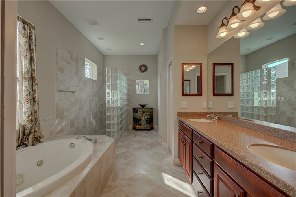 Breathe in relaxation with this gorgeous master bathroom; double-sink vanity, jetted tub, walk-in shower with glass block, lots of natural light, linen closet, and a separate water closet. - Single Family Home for sale at 15109 17th Ave E, Bradenton, FL 34212 - MLS Number is A4425963