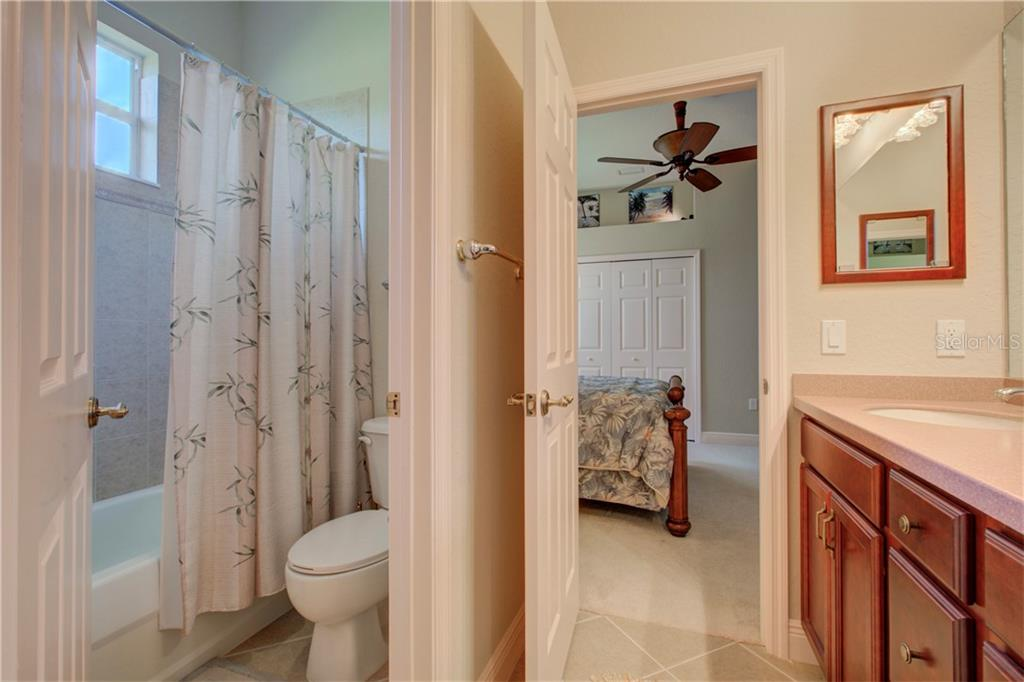 This is the shared/Jack-and-Jill bathroom between the 2nd and 3rd bedrooms.  It includes a double-sink vantity and separated toilet and shower area. - Single Family Home for sale at 15109 17th Ave E, Bradenton, FL 34212 - MLS Number is A4425963