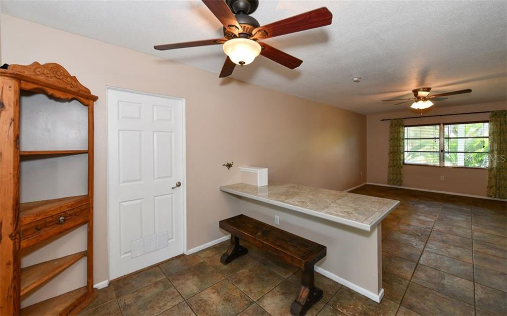 Dining table has tiled top and coordinates with the kitchen countertops. - Single Family Home for sale at 120 23rd Street Ct Ne, Bradenton, FL 34208 - MLS Number is A4438232