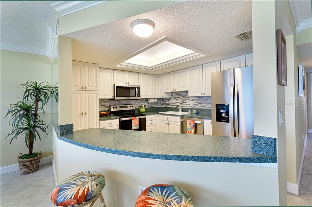Raised panel cabinetry, solid surface counters, lots of storage, slide-out shelving for convenience, tray ceiling with back-lighting .. - Condo for sale at 4706 Independence Dr, Bradenton, FL 34210 - MLS Number is A4443759