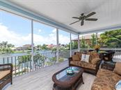 Upstairs screened patio with inviting views of the water and the pool below .Spacious sitting area and dining area - Single Family Home for sale at 7643 Cove Ter, Sarasota, FL 34231 - MLS Number is A4403215